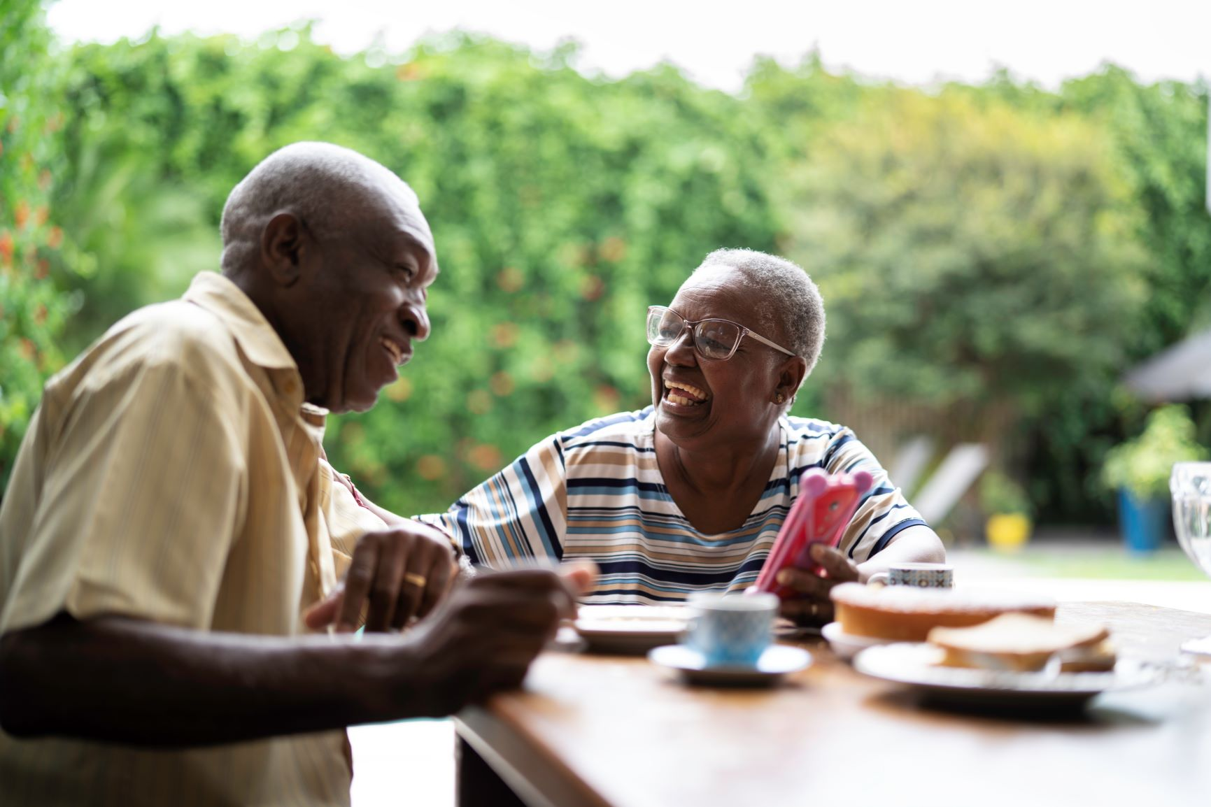 An older man and woman laugh together while enjoying a meal